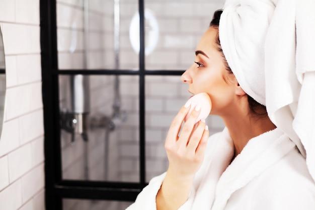 Hübsche frau, die kosmetische eingriffe tut, um für gesichtshaut im badezimmer zu pflegen