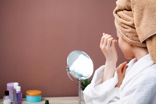 Hübsche frau, die kosmetische eingriffe zu hause vor dem spiegel tut