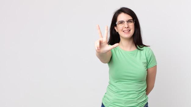 Hübsche frau, die lächelt und freundlich aussieht, die nummer drei oder die dritte mit der hand nach vorne zeigt und herunterzählt