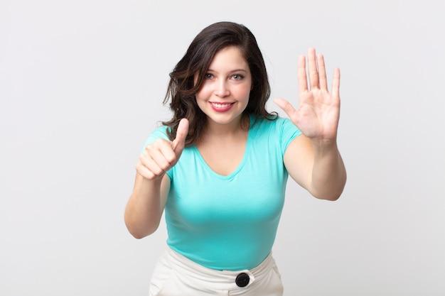 Hübsche frau, die lächelt und freundlich aussieht, die nummer sechs oder sechs mit der hand nach vorne zeigt und herunterzählt