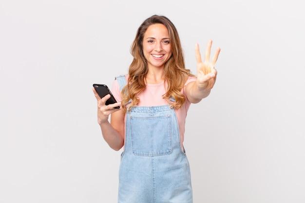 Hübsche frau, die lächelt und freundlich aussieht, nummer drei zeigt und ein smartphone hält holding