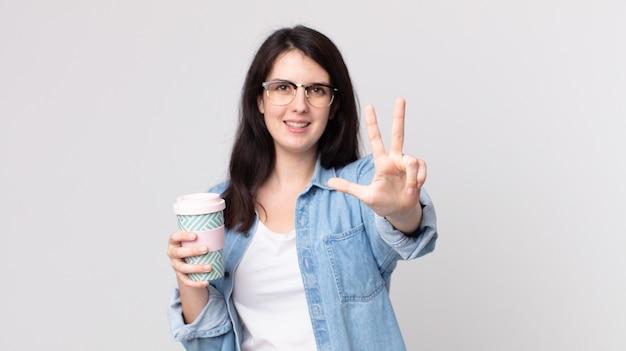 Hübsche frau, die lächelt und freundlich aussieht, nummer drei zeigt und einen kaffee zum mitnehmen hält?