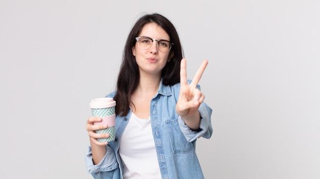Hübsche frau, die lächelt und freundlich aussieht, nummer zwei zeigt und einen kaffee zum mitnehmen hält?