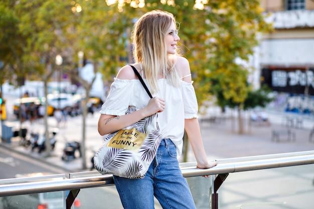 Hübsche frau, die lässiges outfit und ihre studententasche trägt, auf der straße aufwirft und heißen heißen sonnentag des sommers genießt