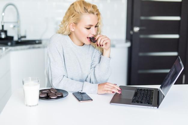 Hübsche frau, die laptop-computer benutzt, während sie am küchentisch sitzt, milch aus einem glas trinkt und kekse isst. morgen.