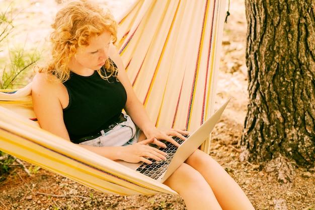 Hübsche frau, die laptop in der hängematte verwendet