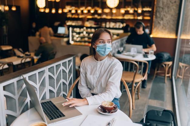 Hübsche frau, die medizinische gesichtsmaske trägt, die laptop verwendet, um zu arbeiten