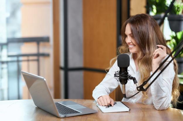 Hübsche frau, die mit anhängern online durch laptop spricht