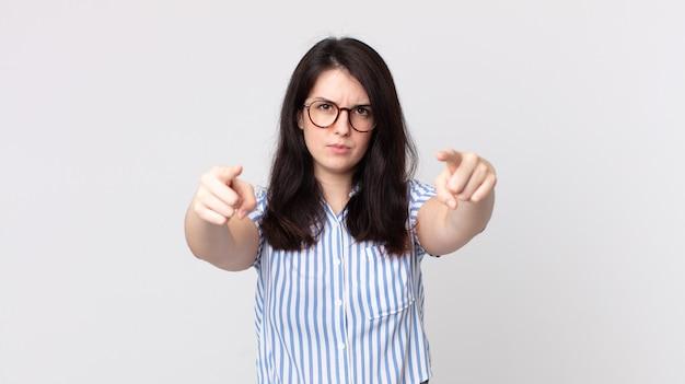 Hübsche frau, die mit beiden fingern und wütendem ausdruck nach vorne auf die kamera zeigt und dir sagt, dass du deine pflicht tun sollst