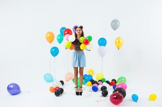 Hübsche frau, die mit bunten heliumballons nach großer partei aufwirft