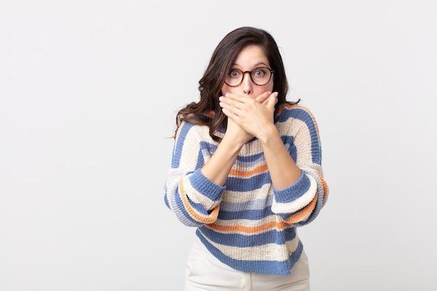 Hübsche frau, die mit einem schockierten, überraschten ausdruck den mund mit den händen bedeckt, ein geheimnis hält oder oops sagt
