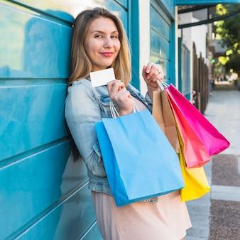 Hübsche frau, die mit einkaufstaschen und kreditkarte steht