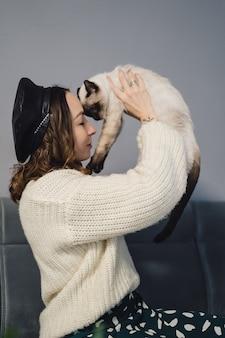Hübsche frau, die mit siamesischer katze spielt