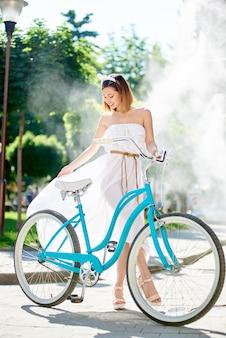 Hübsche frau, die nahe bei einem fahrrad vor einem brunnen aufwirft