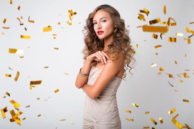 Hübsche frau, die neues jahr im goldenen konfetti feiert