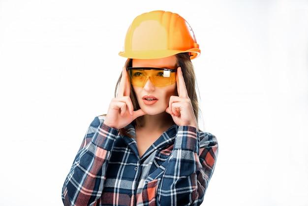 Hübsche frau, die orange schutzhelm und gläser haben kopfschmerzen trägt und finger auf dem kopf lokalisiert auf weiß hält