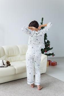 Hübsche frau, die pyjama im wohnzimmer mit weihnachtsbaum trägt