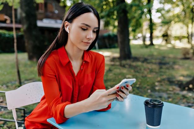 Hübsche frau, die rotes hemd trägt, sitzt auf dem tisch mit smartphone und hört musik