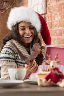 Hübsche frau, die santa claus-hutöffnungs-weihnachtsgeschenk trägt