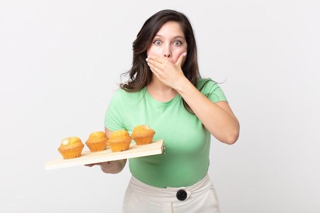 Hübsche frau, die schockiert den mund mit den händen bedeckt und ein muffinsblech hält