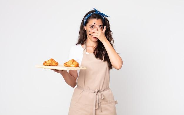 Hübsche frau, die schockiert, verängstigt oder verängstigt aussieht, das gesicht mit der hand bedeckt und ein croissants-tablett hält