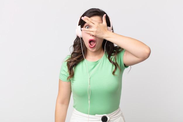 Hübsche frau, die schockiert, verängstigt oder verängstigt aussieht und das gesicht mit der hand bedeckt, die musik mit kopfhörern hört