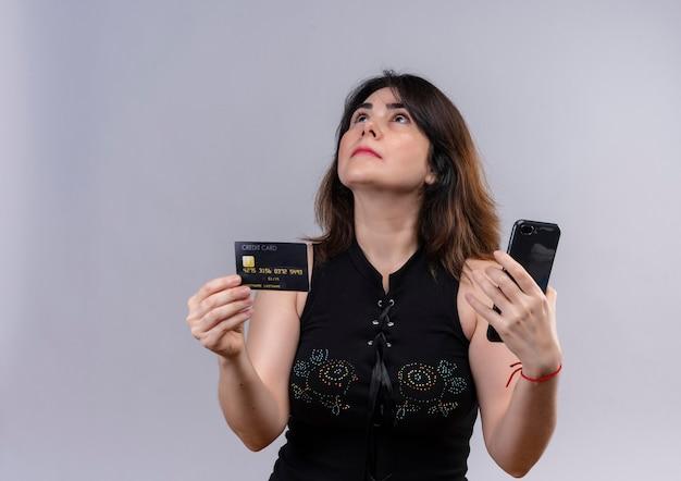 Hübsche frau, die schwarze bluse hält, die kreditkarte und telefon hält, die nachdenklich über grauem hintergrund nachschlagen