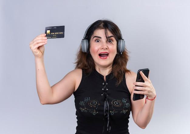 Hübsche frau, die schwarze bluse hält, die telefon und kreditkarte glücklich hält