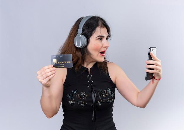 Hübsche frau, die schwarze bluse trägt, die am telefon glücklich überrascht hält, eine kreditkarte zu halten