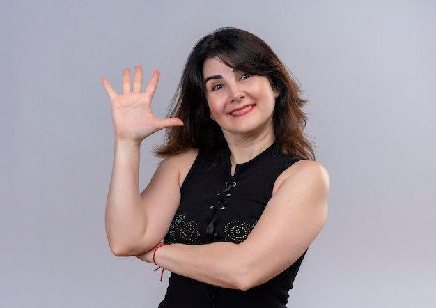 Hübsche frau, die schwarze bluse trägt, die glücklich fünf mit der hand zeigt
