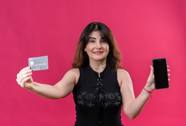 Hübsche frau, die schwarze bluse trägt, die glücklich kreditkarte und telefon hält