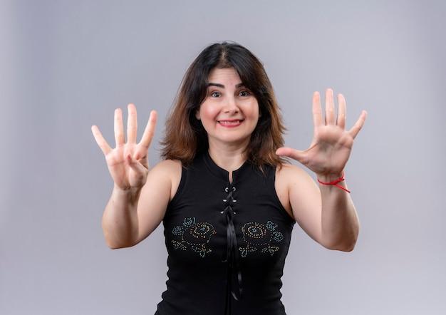 Hübsche frau, die schwarze bluse trägt, die vier und fünf mit den fingern zeigt