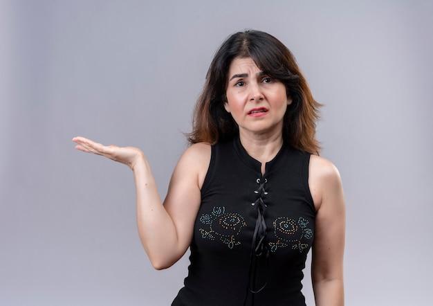 Hübsche frau, die schwarze bluse trägt, hob ihre rechte hand