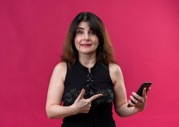 Hübsche frau, die schwarze bluse trägt und überrascht auf das telefon zeigt