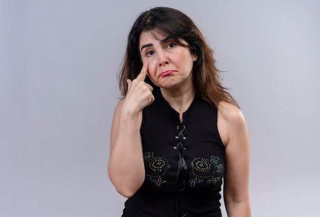 Hübsche frau, die schwarze bluse trägt und unglücklich weint