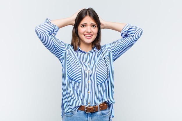 Hübsche frau, die sich gestresst, besorgt, ängstlich oder verängstigt fühlt, mit den händen auf dem kopf und in panik über fehler