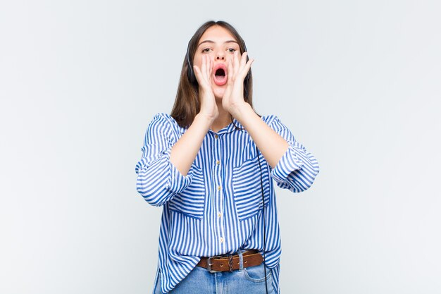 Hübsche frau, die sich glücklich, aufgeregt und positiv fühlt, mit den händen neben dem mund einen großen schrei ausstößt und ruft