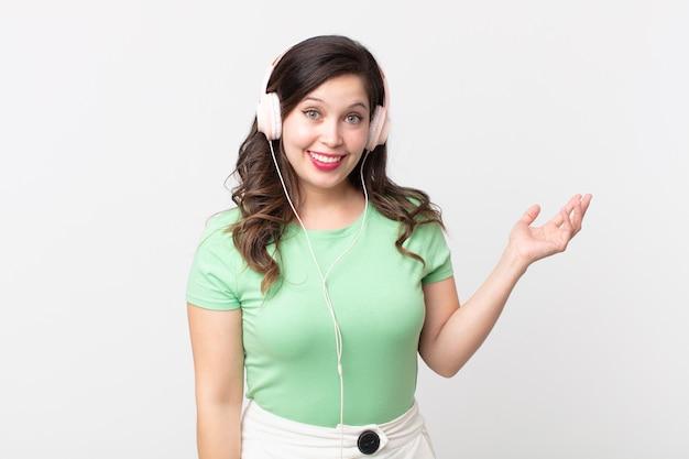 Hübsche frau, die sich glücklich fühlt, überrascht, eine lösung oder idee zu erkennen, musik mit kopfhörern zu hören