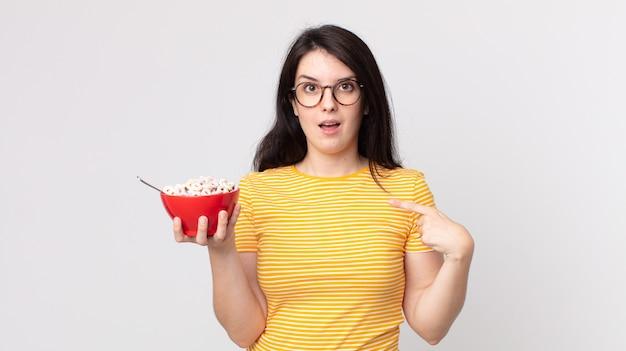 Hübsche frau, die sich glücklich fühlt und auf sich selbst zeigt, aufgeregt und hält eine frühstücksschüssel