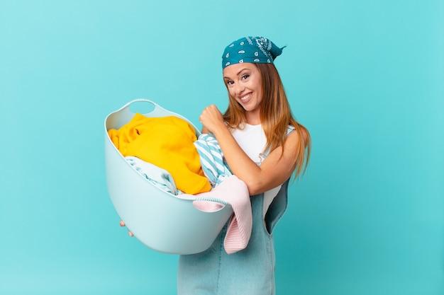 Hübsche frau, die sich glücklich fühlt und sich einer herausforderung stellt oder feiert, einen waschkorb in der hand zu halten