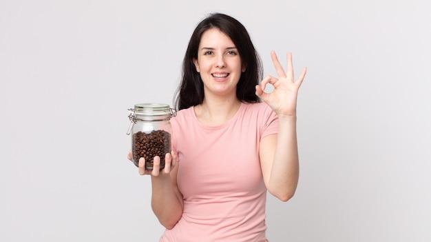 Hübsche frau, die sich glücklich fühlt, zustimmung mit okayer geste zeigt und eine kaffeebohnenflasche hält