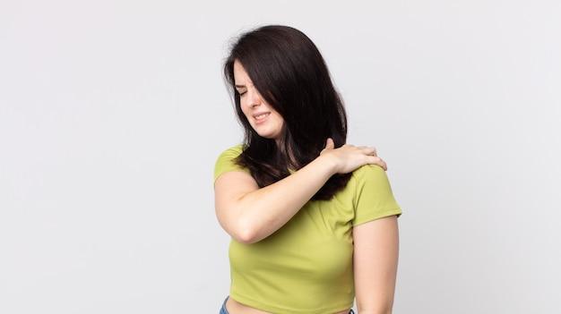 Hübsche frau, die sich müde, gestresst, ängstlich, frustriert und depressiv fühlt und unter rücken- oder nackenschmerzen leidet