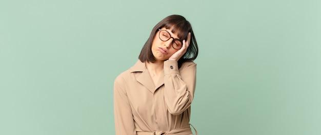 Hübsche frau, die sich nach einer ermüdenden, langweiligen und langweiligen aufgabe gelangweilt, frustriert und schläfrig fühlt und das gesicht mit der hand hält