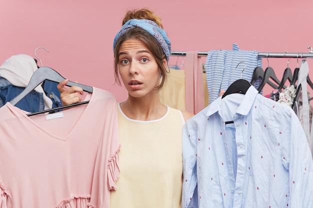 Hübsche frau, die sich nicht sicher ist, ob sie das beste kleid für den abschlussball kaufen soll, und sich zwischen zwei outfits auf kleiderbügeln in ihren händen entscheidet. verwirrte junge frau steht vor dilemma und wählt kleidung in ihrem kleiderschrank