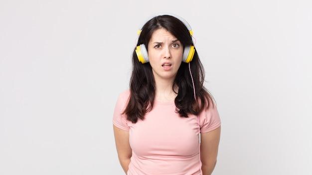 Hübsche frau, die sich verwirrt und verwirrt fühlt, wenn sie musik mit kopfhörern hört