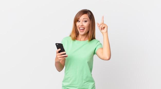 Hübsche frau, die sich wie ein glückliches und aufgeregtes genie fühlt, nachdem sie eine idee realisiert und ein smartphone benutzt hat