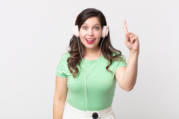 Hübsche frau, die sich wie ein glückliches und aufgeregtes genie fühlt, nachdem sie eine idee verwirklicht hat, musik mit kopfhörern zu hören