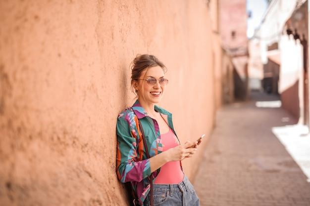 Hübsche frau, die smartphone auf der straße von marrakesch verwendet