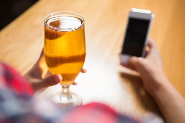 Hübsche frau, die smartphone verwendet und ein bier isst