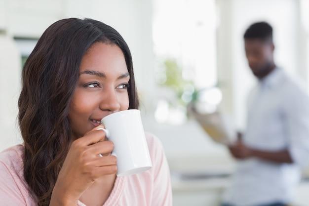 Hübsche frau, die tasse kaffee isst